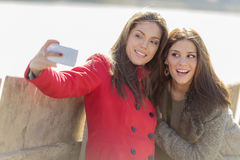 Femmes prenant la photo avec le téléphone portable Photographie stock
