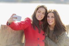 Femmes prenant la photo avec le téléphone portable Images libres de droits