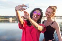 Femmes prenant la photo d'elle-même, selfie aux vacances heureuses d'image de mode de vie de plage de filles ensoleillées de meil Photos libres de droits