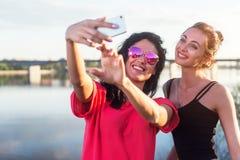 Femmes prenant la photo d'elle-même, selfie aux vacances heureuses d'image de mode de vie de plage de filles ensoleillées de meil Photo libre de droits
