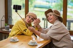 Femmes prenant le selfie en café Photo stock