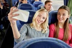 Femmes prenant le selfie par le smartphone dans l'autobus de voyage Images libres de droits