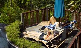 Femmes prenant un bain de soleil près de la piscine image libre de droits