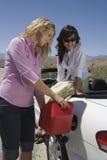 Femmes réapprovisionnant en combustible le carburant dans la voiture Images stock