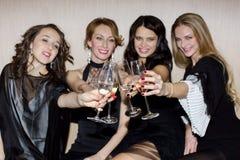 Femmes résonnant des verres et le sourire Photo stock