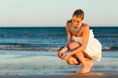 Femmes recherchant des coquilles de mer dans le coucher du soleil romantique Photo stock