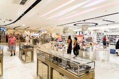Femmes recherchant le parfum de luxe dans l'intérieur de centre commercial Photographie stock libre de droits
