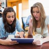 Femmes regardant choquées le PC de comprimé dans la cantine Photos stock