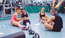 Femmes regardant des amis de smartphone et de couples Photographie stock libre de droits
