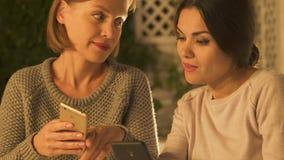 Femmes regardant la page sociale de réseau de leurs amis, discutant le plan rapproché de rumeurs banque de vidéos