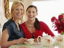Femmes reposant la table de salle à manger Photographie stock libre de droits