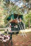 Femmes reposant se situer dans la tente au-dessus de 4x4 et le regard Photographie stock libre de droits