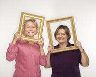 Femmes retenant des cadres de tableau. Photos stock