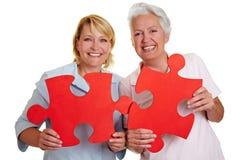 Femmes retenant des parties de puzzle denteux Photographie stock