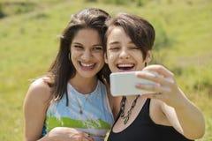 Femmes riant et ayant l'amusement avec le smartphone Photo libre de droits