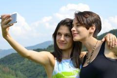 Femmes riant et ayant l'amusement avec le smartphone Photographie stock libre de droits