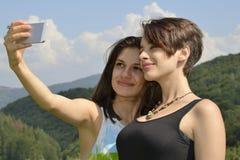 Femmes riant et ayant l'amusement avec le smartphone Photographie stock