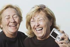 Femmes riantes avec l'appareil photo numérique Photo stock