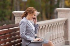 Femmes riantes d'affaires avec l'ordinateur portable Photo libre de droits