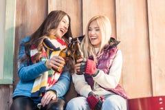 Femmes riantes faisant tinter des bouteilles à bière sur le porche Photos stock