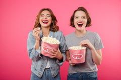 Femmes riantes gaies mangeant le film de montre de maïs éclaté Images libres de droits