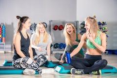 Femmes riantes heureuses après la formation dans parler de gymnase Photographie stock