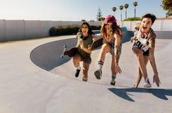 Femmes riantes montant une rampe de planche à roulettes Photos stock