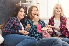 Femmes riantes observant le film à la maison Photos stock