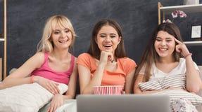 Femmes riantes observant le film à la maison Image libre de droits