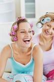 Femmes riantes utilisant des rouleaux de cheveu sur le sofa Photographie stock