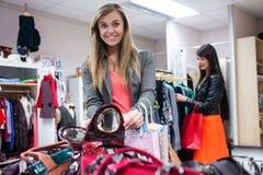 Femmes sélectionnant des sacs et des vêtements tout en faisant des emplettes image libre de droits