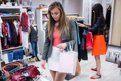 Femmes sélectionnant des sacs et des vêtements tout en faisant des emplettes images stock