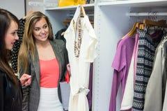 Femmes sélectionnant une robe tout en faisant des emplettes pour des vêtements Photographie stock
