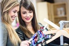 Femmes sélectionnant une robe tout en faisant des emplettes pour des vêtements Photos libres de droits