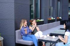 Femmes s'asseyant au café près des tasses de café sur la table Image stock