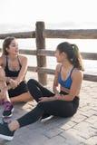Femmes s'asseyant et parlant à la plage Photo stock