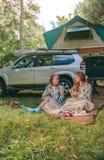 Femmes s'asseyant sous la couverture avec 4x4 sur le fond Images stock