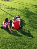 Femmes s'asseyant sur l'herbe Image libre de droits