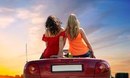 Femmes s'asseyant sur la voiture convertible au-dessus du coucher du soleil de ville Images libres de droits