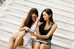 Femmes s'asseyant sur les escaliers en dehors de et à l'aide du téléphone portable Photos libres de droits