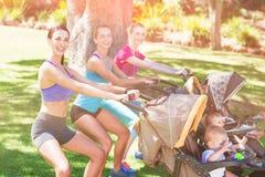 Femmes s'exerçant avec la poussette de bébé Photos stock