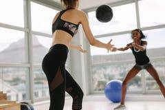 Femmes s'exerçant avec le medicine-ball dans le gymnase Image stock