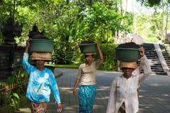 Femmes s'inquiétant des paniers sur leurs têtes au temple indou de Balinese de Tirta Empul dans Bali, Indonésie Photo stock