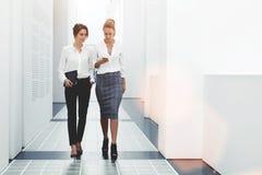 Femmes sûres lisant des informations sur des actualités de finances tout en marchant dans le couloir de société pendant la pause, Photographie stock libre de droits