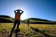 Femmes se baladantes trimardant en montagnes de lever de soleil Photographie stock