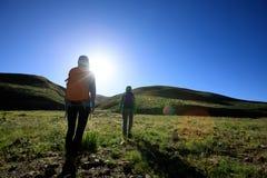 Femmes se baladantes trimardant en montagnes de lever de soleil Photos stock