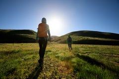 Femmes se baladantes trimardant en montagnes de lever de soleil Photographie stock libre de droits