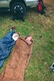 Femmes se reposant à l'intérieur de des sacs de couchage avec 4x4 dessus Photo stock