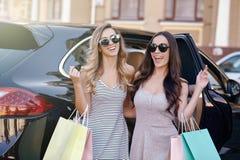 Femmes se tenant à l'extérieur de voiture avec des sacs à provisions photo libre de droits