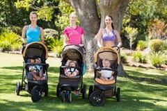 Femmes se tenant avec la poussette de bébé images stock